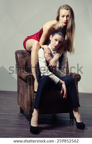 Beautiful lesbian flirting couple on the chair. - stock photo