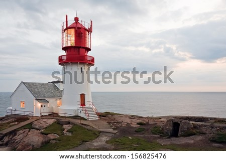 beautiful lighthouse on the edge of rocky sea coast, South Norway, Lindesnes Fyr beacon - stock photo