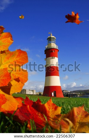 beautiful lighthouse with flying autumn leaves, Plymouth, UK - stock photo