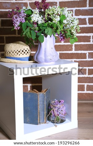 Beautiful lilac flowers in vase, on stand, on color wall background