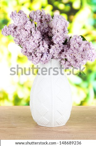 Beautiful lilac flowers on table on bright background - stock photo