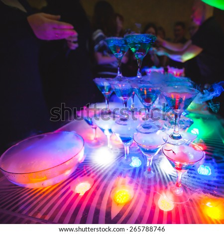 Beautiful line of different colored cocktails with smoke on a open air party, tequila, martini, vodka, and others on decorated catering bouquet table on open air party with smoke