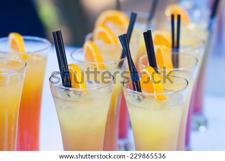 Beautiful line of different coloured cocktails with smoke on a open air party, tequila, martini, vodka, and others on decorated catering bouquet table on open air party  - stock photo