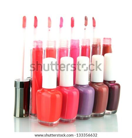 beautiful lip glosses and nail polish bottles, isolated on white - stock photo