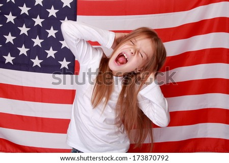Beautiful little American hands covering her ears against the background of the American flag