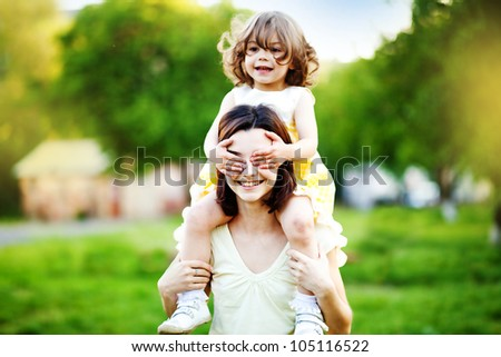 beautiful little and happy daughter with her hands on eyes of her mother. - stock photo
