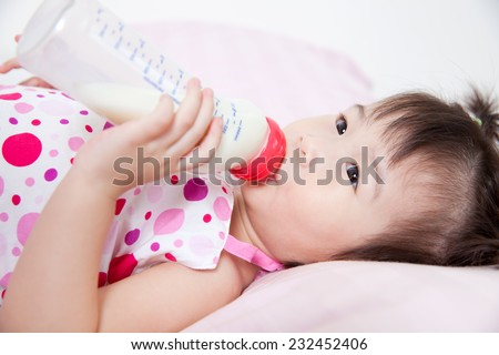 Beautiful little asian girl lying and suck up milk bottle in bed