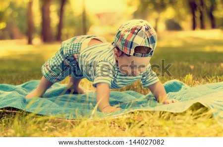 Beautiful little baby boy doing push-ups on the mat on the grass in the park - stock photo