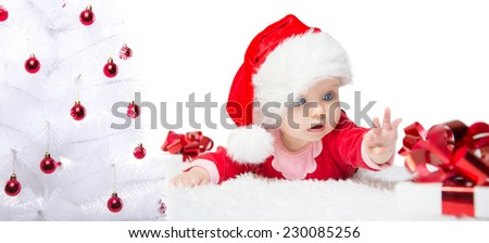 Beautiful little baby celebrates Christmas. New Year's holidays. Baby in a Christmas costume with gift. Christmas tree