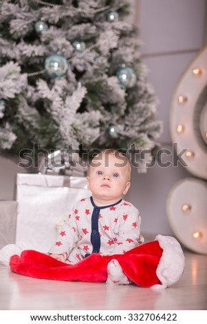 Beautiful little baby celebrates Christmas. New Year's holidays. Baby in a Christmas costume with gift - stock photo
