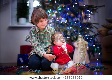 Beautiful little baby girl and her cute brother playing together under a Christmas tree in a dark living room - stock photo