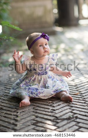 Beautiful little baby girl at 8 mo sits outside in the dress