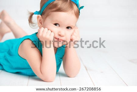 beautiful little baby girl in a turquoise dress on the floor near a white brick wall - stock photo