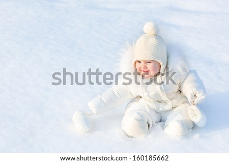 Beautiful little baby girl sitting in white snow wearing a warm jacket and knitted hat - stock photo