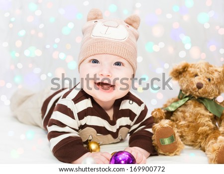 Beautiful little baby in the bear hat with ears, lays with toys and smiles.