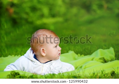 Beautiful little baby lying on the grass in the park - stock photo