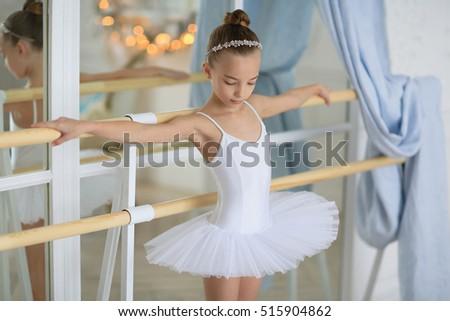Beautiful little ballerina white tutu in classes at the ballet school