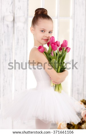 beautiful little ballerina with a bouquet of pink tulips - stock photo