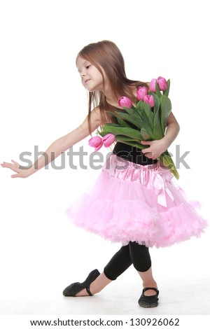Beautiful little ballerina with long healthy hair dancing ballet with tulips - stock photo