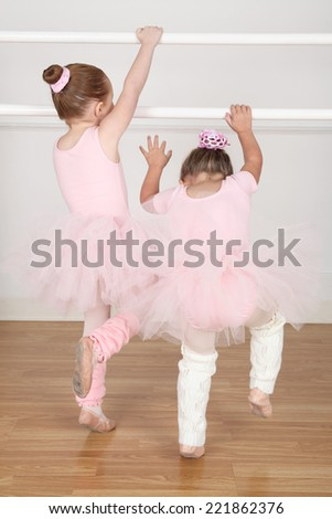 Beautiful little ballet dancers at the dance studio barre - stock photo