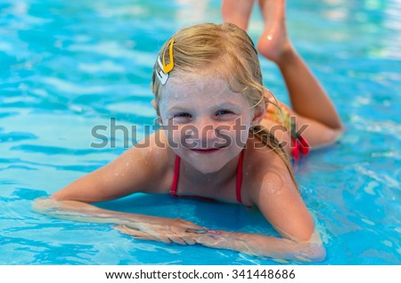 beautiful little blond girl lying in shallow water in the swimming  pool