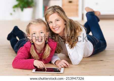 Beautiful little blond girl lying on the living room floor with her mother as they play games on a tablet-pc, both are looking up smiling at the camera - stock photo