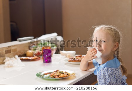 Beautiful little blond girl wiping her mouth on a napkin as she sits at the table enjoying a large plate of homemade Italian pizza - stock photo