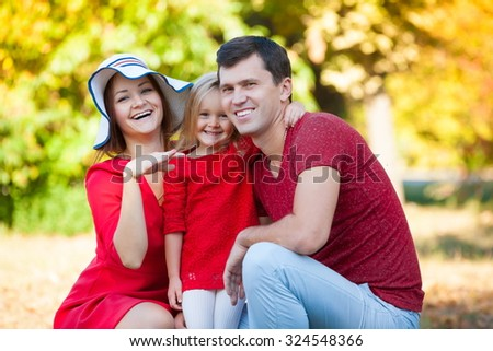 Beautiful little blonde girl and her father and mother, has happy fun cheerful smiling face, red clothes. Family portrait nature.  - stock photo
