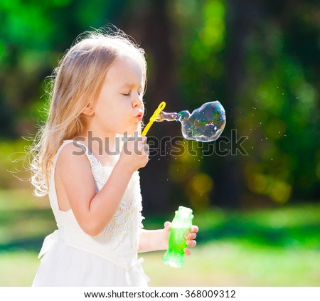 Beautiful little blonde girl, has happy fun cheerful smiling face, white dress, soap bubble blower. Portrait nature.  - stock photo