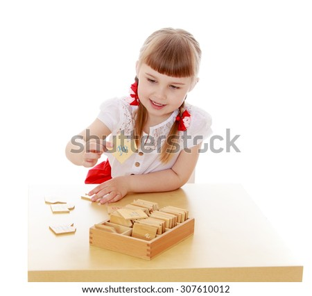 Beautiful little blonde girl with short bangs and grey eyes sitting at the table in the Montessori environment-Isolated on white background - stock photo