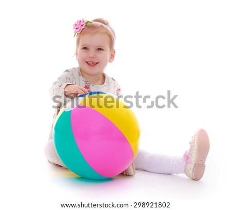 Beautiful little blonde girl with short hair, white dress and white stockings is sitting on the floor in front of her big bouncy striped ball, girl playing with their parents on the beach at the sea