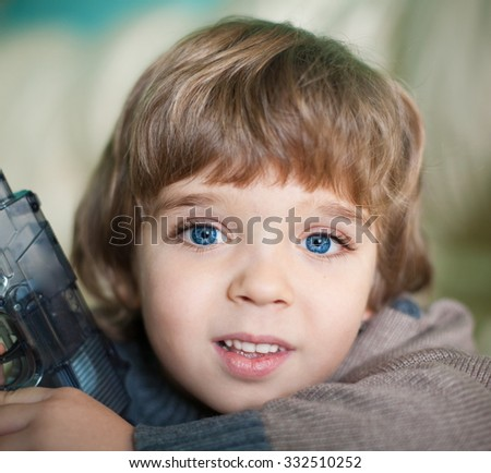 Beautiful little blonde hair boy, has happy fun cheerful smiling face, blue eyes, long eyelashes. Portrait nature.  - stock photo