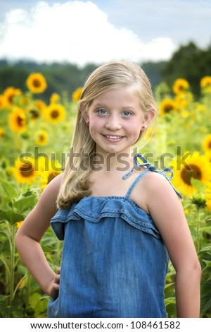 Beautiful little blue-eyed, blonde girl in denim top standing in front blooming sunflower field