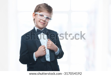 Beautiful little boy in a nice tuxedo and sunglasses goes to school. Stylish baby laughing and looking at the camera. Children portrait - stock photo