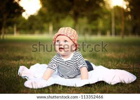 Beautiful little boy lies on the coverlet in summer park - stock photo