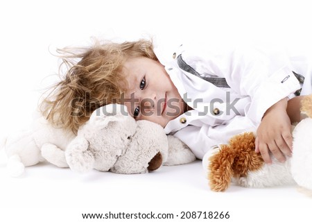 Beautiful little boy lying on the floor holding plush toys - stock photo