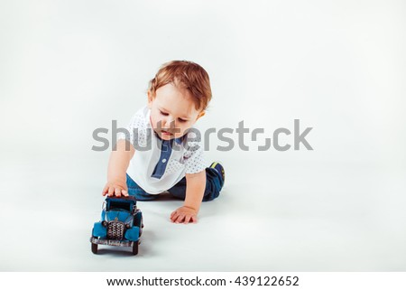 beautiful little boy playing with car  in the studio