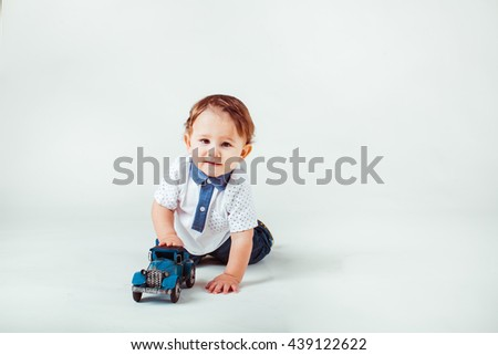 beautiful little boy playing with toys in the studio