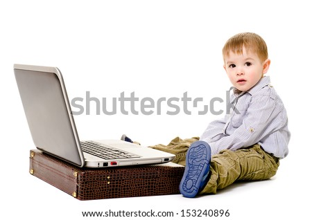 Beautiful little boy sitting on the floor with a laptop - stock photo