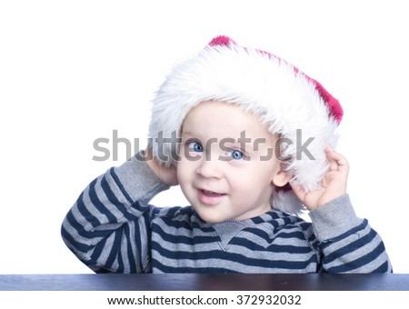 Beautiful little boy with blond hair and blue eyes in a red Christmas hat on his head.