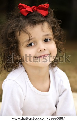 Beautiful little brown eyed brunette girl with curly hair and a red bow. - stock photo
