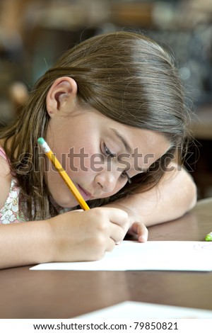 Beautiful  little brunette girl writing with pencil and paper in classroom - stock photo