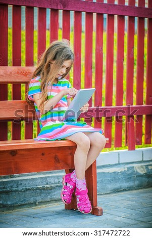 Beautiful little calm girl playing on Tablet PC, sitting on bench. - stock photo