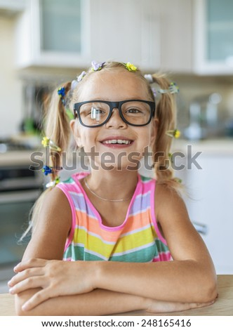 Beautiful little cheerful girl in glasses sitting at kitchen table.