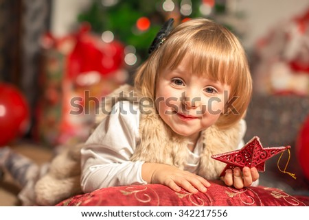 Beautiful little child celebrates Christmas. New Year's holidays. Indoor winter girl portrait