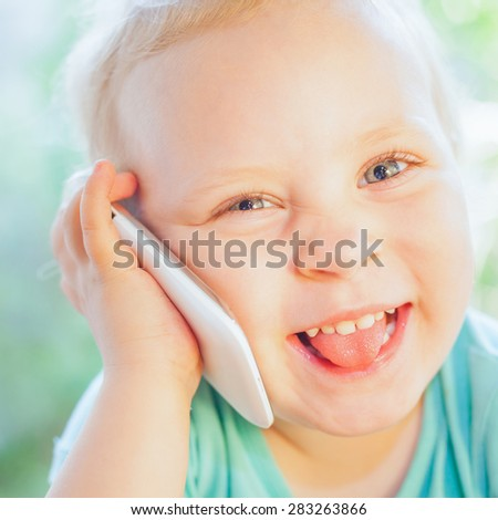 Beautiful little child talking by mobile phone with her mother. Girl is blonde with very beautiful eyes on a green background and she is happy. Square orientation