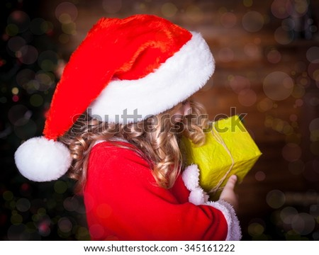 Beautiful little curly blonde girl, has happy fun cheerful smiling face profile, has red Christmas hat Santa Claus, holding a gift box. Portrait holiday. Fairy night. - stock photo