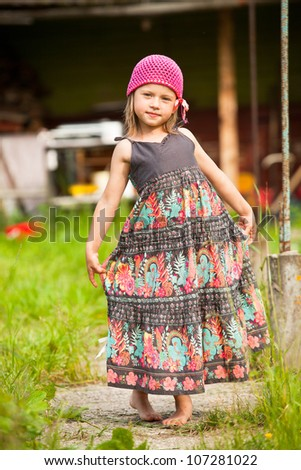 Beautiful little five-year girl posing for the camera in the yard of a village house. - stock photo