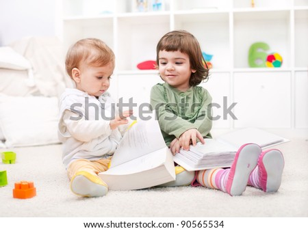 Beautiful little girl and baby boy reading indoors - stock photo
