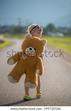 Beautiful little Girl and her teddy bear on the road - stock photo